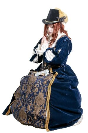 A woman dressed as a renaissance aristocrat in authentic dress as she prays photo
