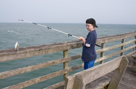 A boy fishing off a pier at the ocean photo
