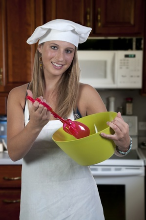 A beautiful woman chef holding a salad bowl and tongs Stock Photo - 10255065