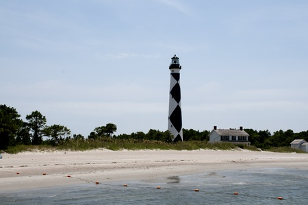A historic lighthouse guiding ships away from rocky shoals. photo