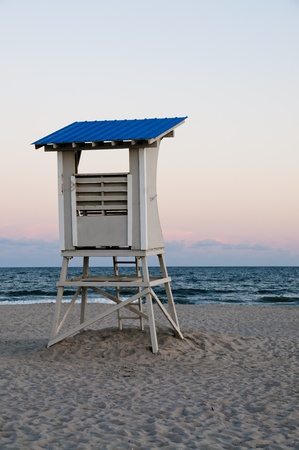 A towering lifeguard station on a sandy beach photo