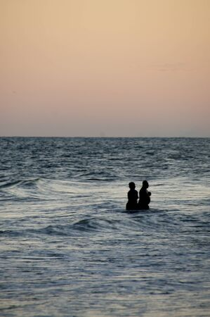 dipping: A couple of late evening silhouetted swimmers at the beach Stock Photo