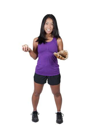 A beautiful Asian woman catching a baseball at a ball field photo