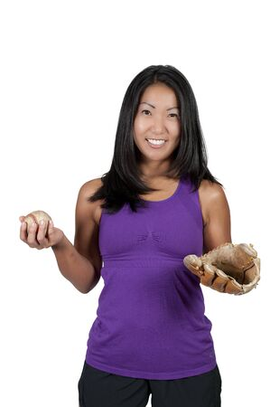 A beautiful Asian woman catching a baseball at a ball field photo