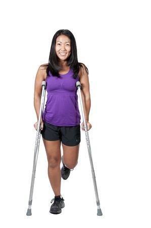医療松葉杖のセットを使用して歩く彼女の助けする美しいアジアの女性