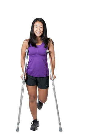crutch: A beautiful Asian woman using a set of medical crutches to help her walk