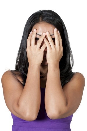 A beautiful young scared or surprized Asian woman looking through her hands photo