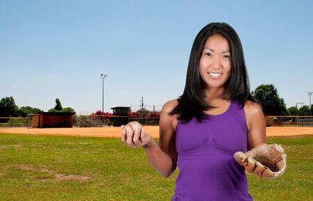 outfield: A beautiful Asian woman catching a baseball at a ball field