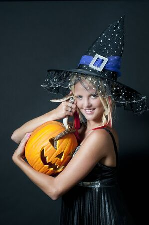 A beautiful young witch with a snake in a jack-o-lantern photo