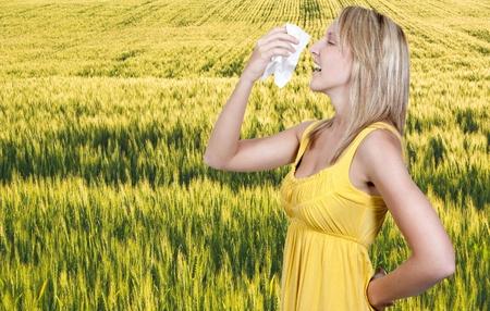 Een mooie vrouw met een verkoudheid, hooikoorts of allergie blazen haar neus of niezen