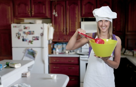 A beautiful woman chef holding a salad bowl and tongs photo