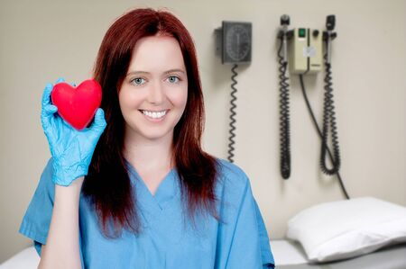 A female cardiologist woman doctor holding a red heart photo