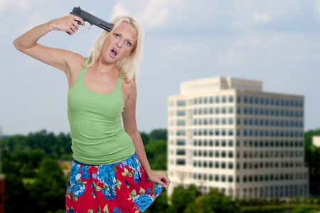 death head holding: A beautiful woman holding a gun to her head threatening suicide Stock Photo