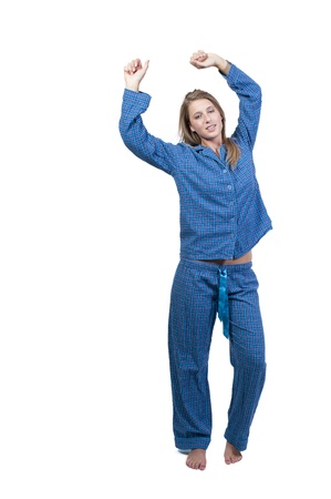 sleeping girl: A young stretching woman waking up in her pajamas in the morning Stock Photo