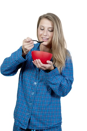A beautiful woman wearing pajamas eating food from a bowl Stok Fotoğraf - 10857655