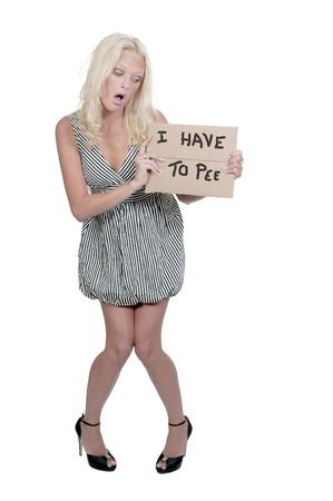 Una joven y bella mujer sosteniendo un cartel que dice que tengo que orinar Foto de archivo