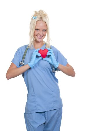 blonde minority: A female cardiologist woman doctor holding a red heart Stock Photo