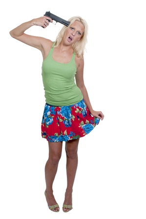 holding gun to head: A beautiful woman holding a gun to her head threatening suicide Stock Photo