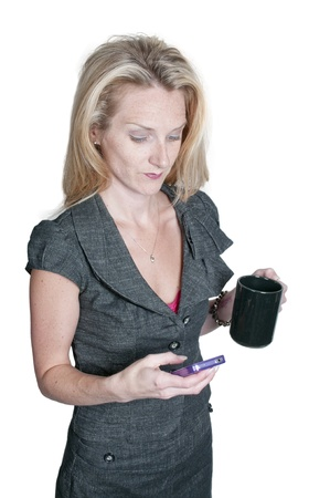 A beautiful young woman using a cell phone for texting while drinking a cup of coffee photo