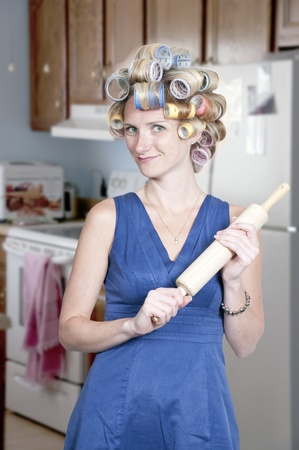 A beautiful young woman housewife with curlers in her hair holding a rolling pin
