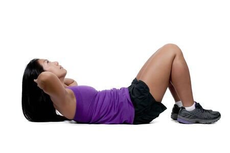 A beautiful young Asian woman exercising by doing crunches Imagens