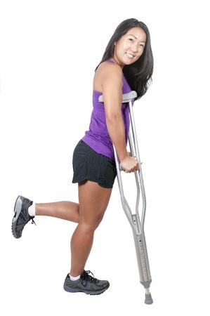 pierna rota: Una hermosa mujer asiática utilizando un conjunto de médicos muletas para ayudarla a caminar Foto de archivo
