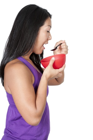A beautiful Asian woman eating food from a bowl photo