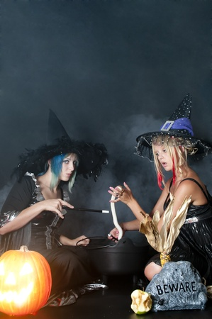 Beautiful young women witches with a snake in a jack-o-lantern Zdjęcie Seryjne