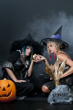 Beautiful young women witches with a snake in a jack-o-lantern Banco de Imagens