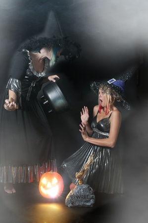 Beautiful young women witches with a snake in a jack-o-lantern photo