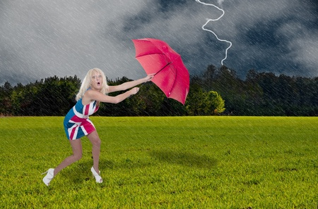 precipitation: A beautiful young woman holding an umbrella in a rain and lightning thunderstorm