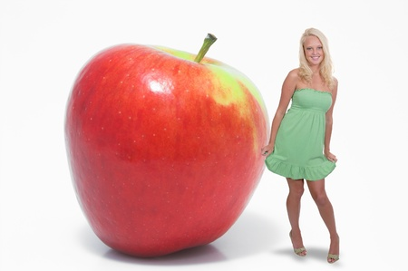 winesap apple: A beautiful woman standing beside a whole red delicious apple waiting to be eaten.