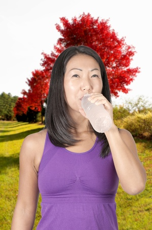 A beautiful young woman water from a plastic bottle photo