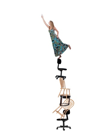 A woman standing on chairs and stools to change a light bulb.