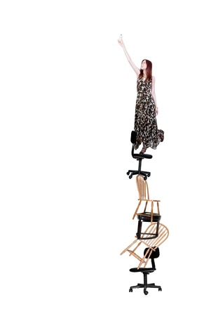 A woman standing on chairs and stools to change a light bulb. photo