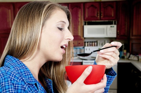 A beautiful woman wearing pajamas eating food from a bowl photo
