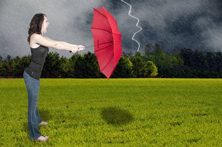 A beautiful young woman holding an umbrella in a rain and lightning thunderstorm