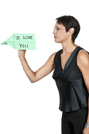 A woman throwing a paper airplane that says I Love You Stock Photo