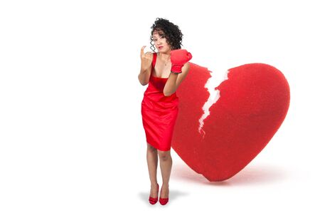 A beautiful black woman in a red dress wearing a boxing glove in front of a broken heart photo