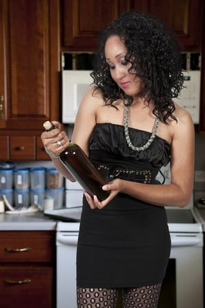 A beautiful African American woman holding wine glasses and a wine bottle photo