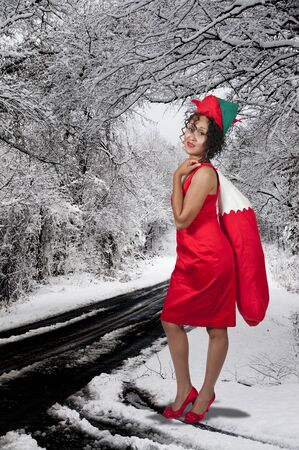 a beautiful woman elf holding a big Christmas stocking photo
