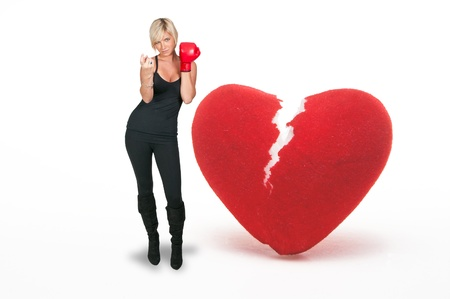 hither: A beautiful woman in wearing a boxing glove in front of a broken heart - heartbreaker Stock Photo