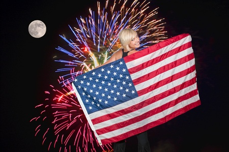 american flag fireworks: A beautiful young woman holding an American flag during a fireworks display during a full moon