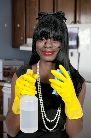 An African American glove wearing beautiful woman or maid cleaning house with a sponge and spray bottle with cleaner Stock Photo - 11172237