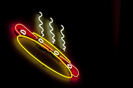 A colorful electic neon hotdog light sign