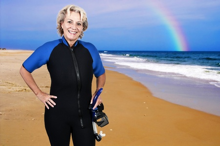 An older woman in scuba wet suit with a mask and snorkle photo