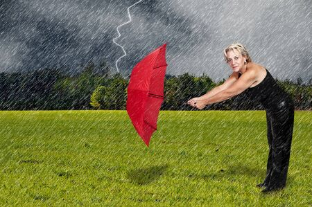 downpour: A middle aged woman holding an umbrella in a rain lightening storm