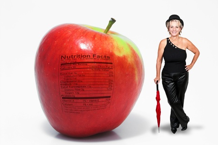 A middle aged woman standing with a whole red delicious apple with a nutrition label photo