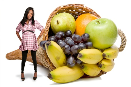 Beautiful young pregnant black African American wooman and a cornucopia basket filled with delicious fresh fruit photo