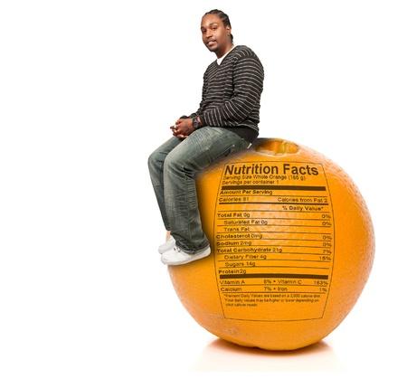 Black African American man sitting on an orange fruit with nutrition facts Reklamní fotografie